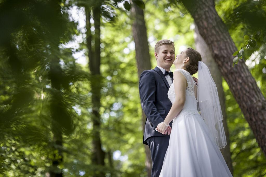 Rafał Kowalski Fotograf Ślubny opinie - Para młoda w trakcie pleneru ślubnego w zielonym lesie nad jeziorem w Otominie koło Gdańska