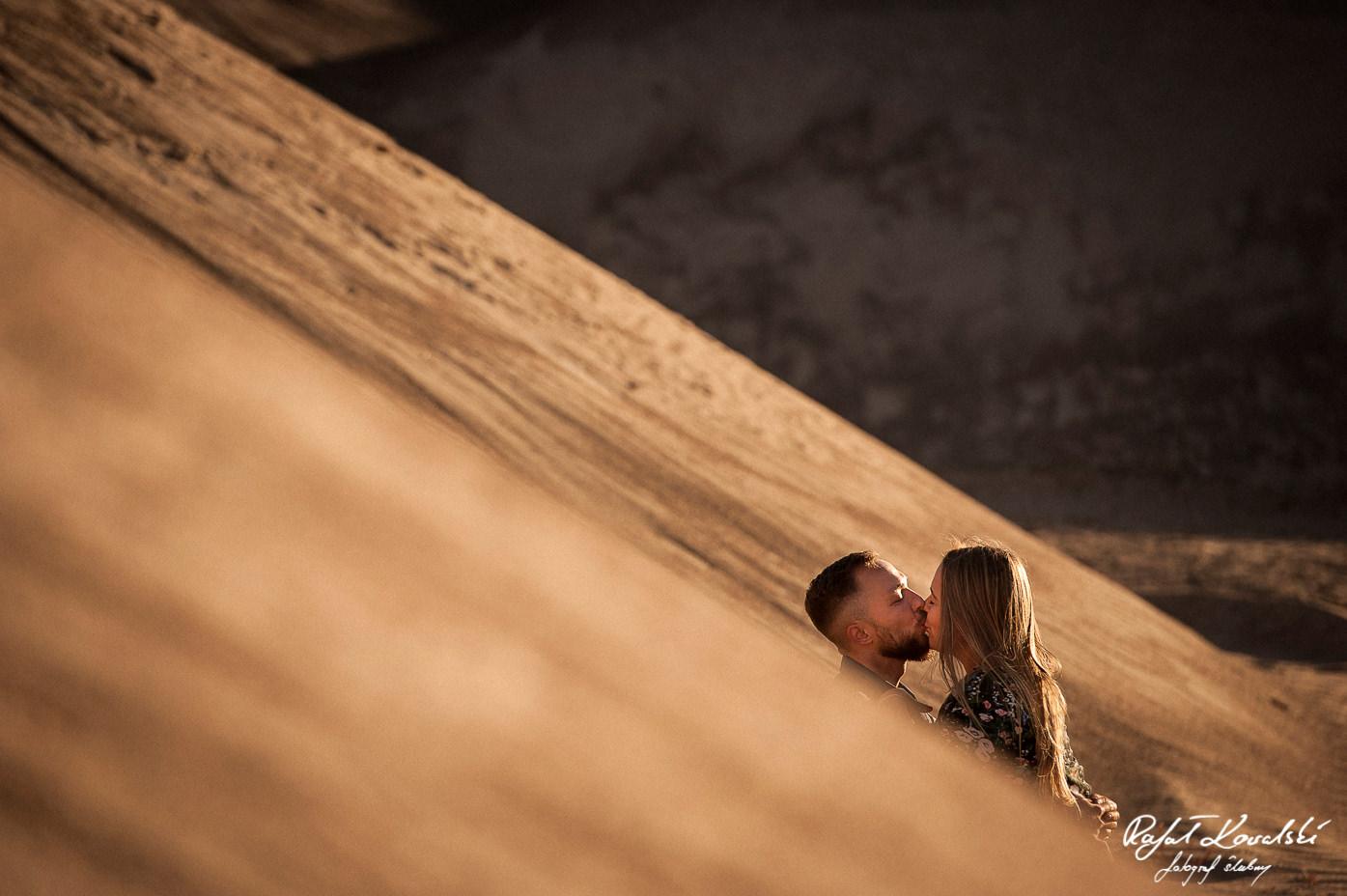 Sesja na pustyni pocałunek narzeczonych pośród złotych piasków fotograf gdańsk Rafał Kowalski