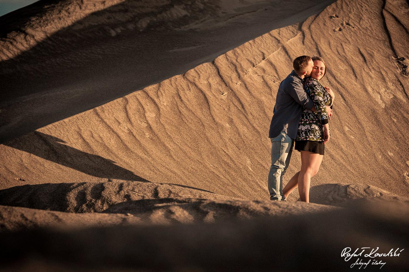 gra złotego światła i cieni na piaskowym tle podkreśla romantyczny charakter sesji narzeczeńskiej
