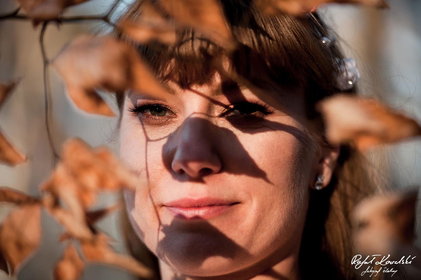 gra światła i cieni z gałązki z zaschnietymi liśćmi na twarzy panny młodej w trakcie pleneru ślubnego w Gdyni