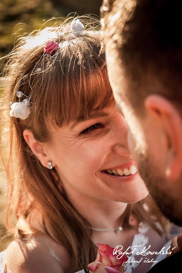 ujęcie z bliska na roześmianą buzię panny młodej wpatrującej się w oczy męża na plenerze ślubnym w Gdyni