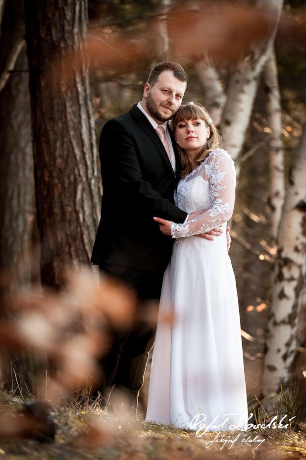 klasyczny kard z parą młodą w objęciach na plenerze ślubnym