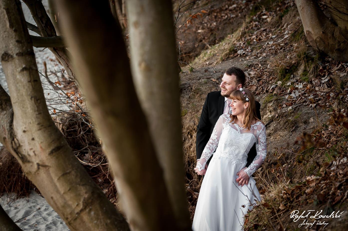 sesja ślubna wśród drzew pochylających się nad plazą w Gdyni