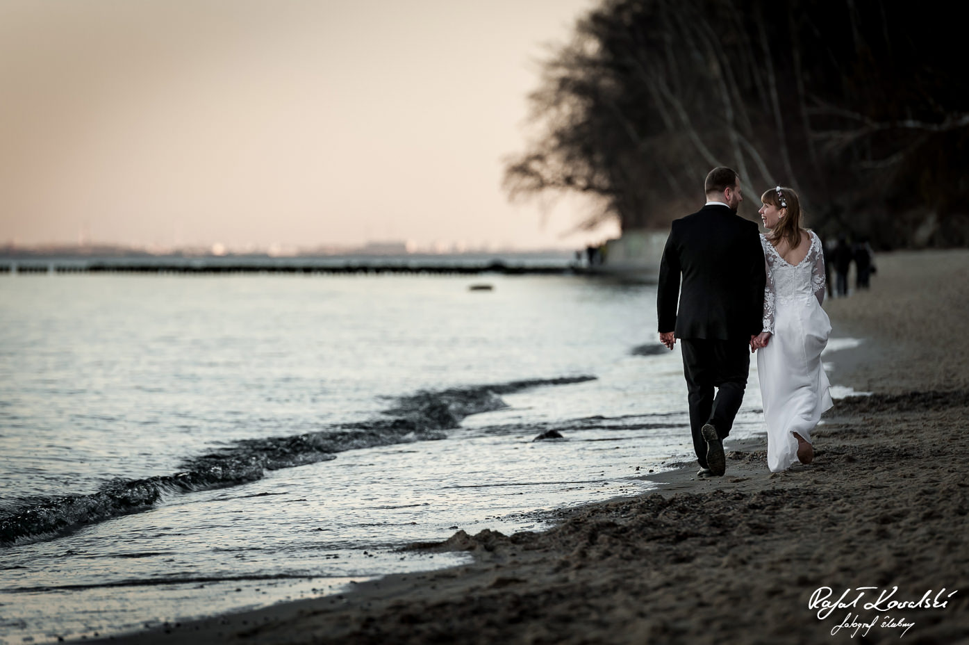 młodzi małżonkowie odchodzą w dal po zakończonej sesji plenerowej na plazy w Gdyni