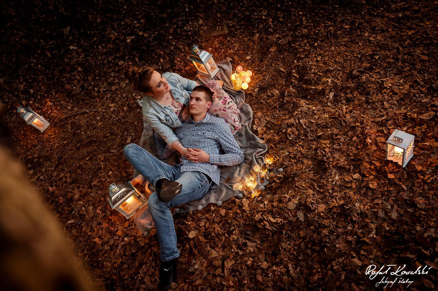 Piknik w lesie pośród lampionów. Zakochana para na kocyku w trakcie sesji narzeczeńskiej