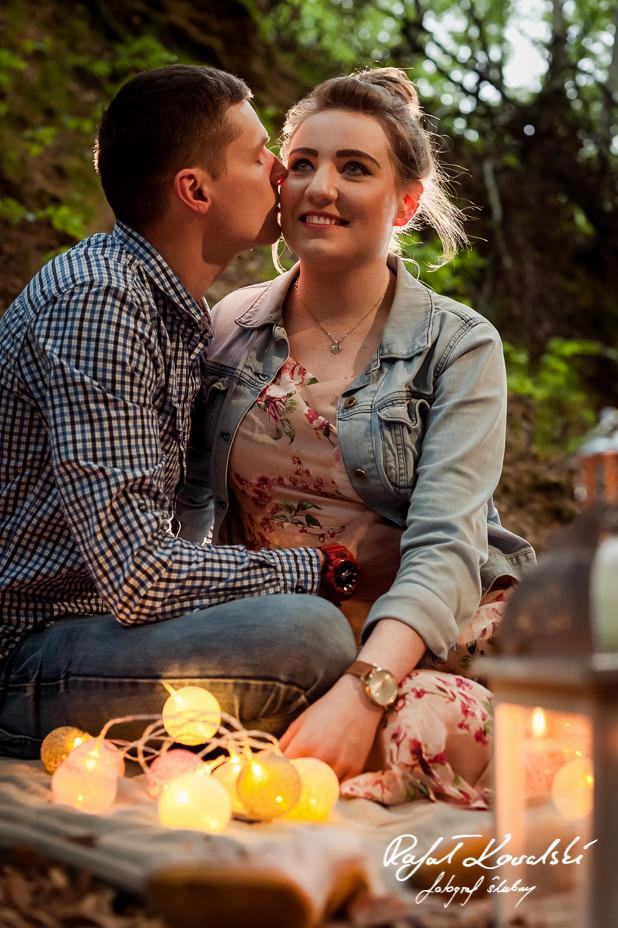 Nieśmiały pocałunek w śiwetle lampionów podczas sesji zdjęciowej w plenerze