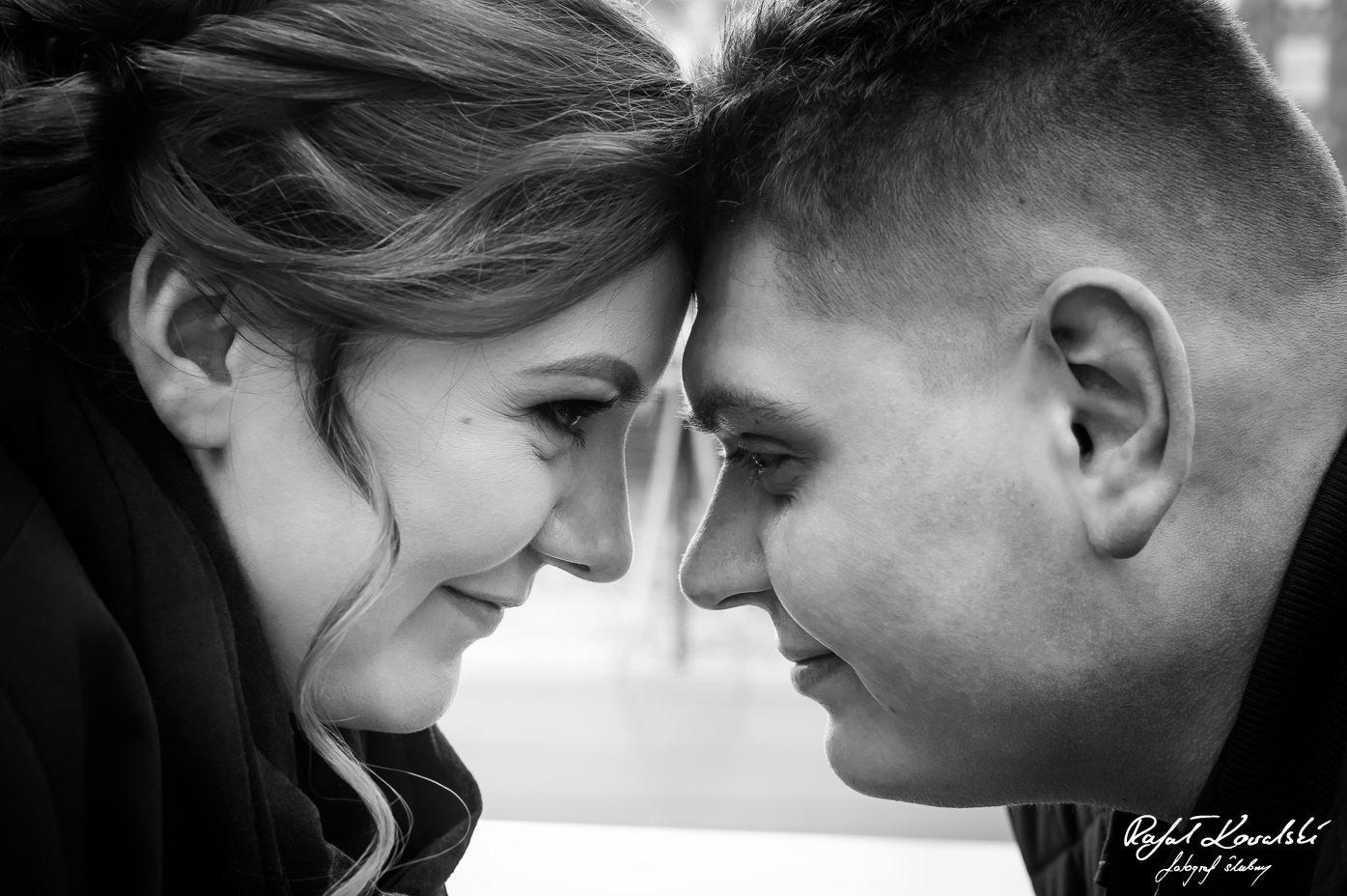 potret pary - dwie uśmiechnięte i zakochane w sobie buzie stykające się czołami