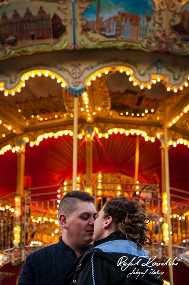 sesja narzeczeńska Gdańsk - czuły pocałunek na tle oświetlonej karuzeli retro