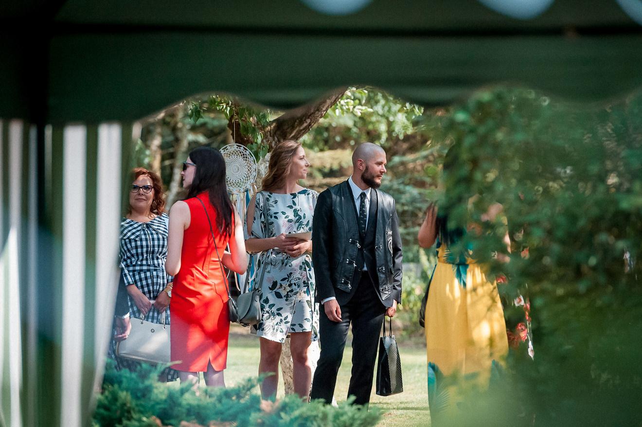 Goście weselni czekujący na ślub w plenerze