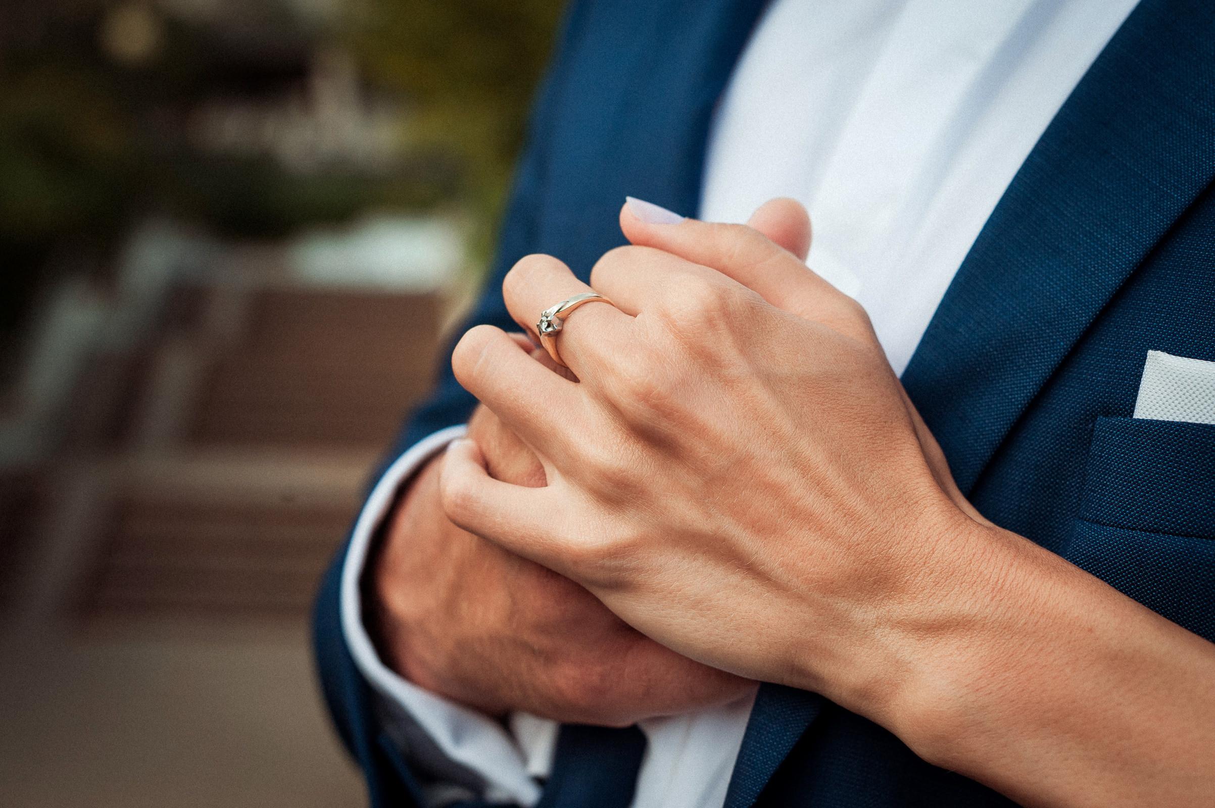 pierścionek zaręczynowy na palcu dłoni ściskanej przez Pana Młodego - sesja zdjęciowa w plenerze