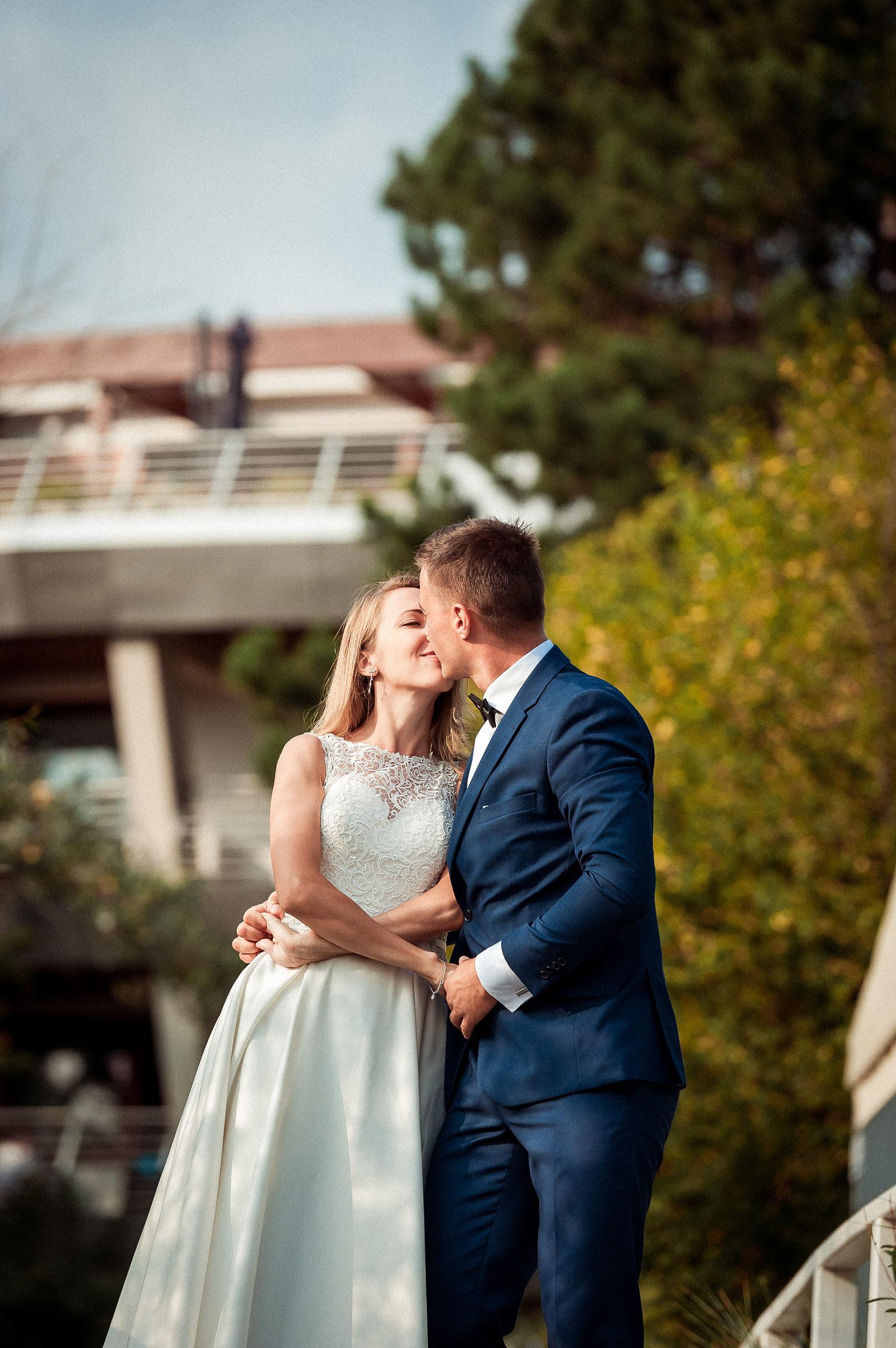 Czuły pocałunek Pary Młodej na tle hotelu Dom Zdrojowy w Jastarni