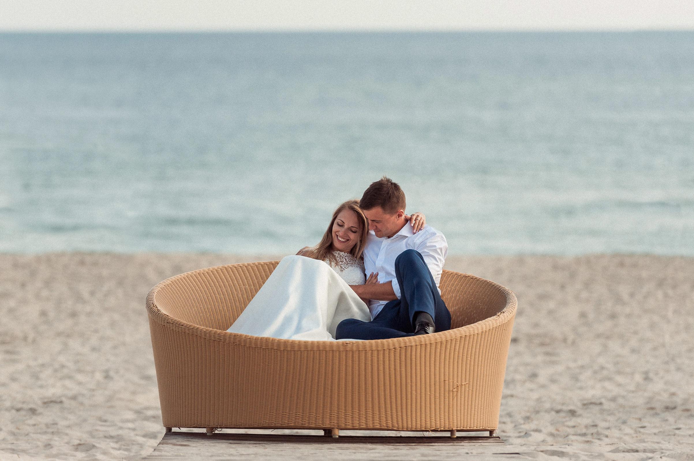 zakochani leżą na szerokim ratanowym koszu na piaszczystej plaży
