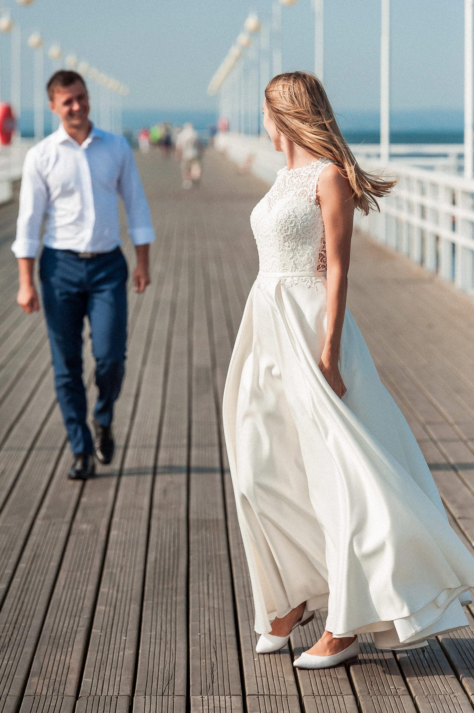 panna młoda z wdziękiem kokietuje pana młodego na sesji ślubnej w Juracie