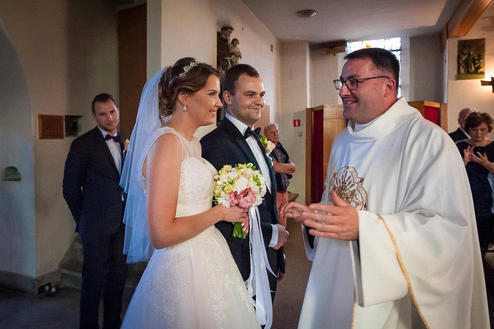 Wpólna droga pary młodej do ołtarza najczęściej zaczyna się od powitania przez księdza - to wzruszający i sympatyczny moment, który warto ująć w reportażu ślubnym.