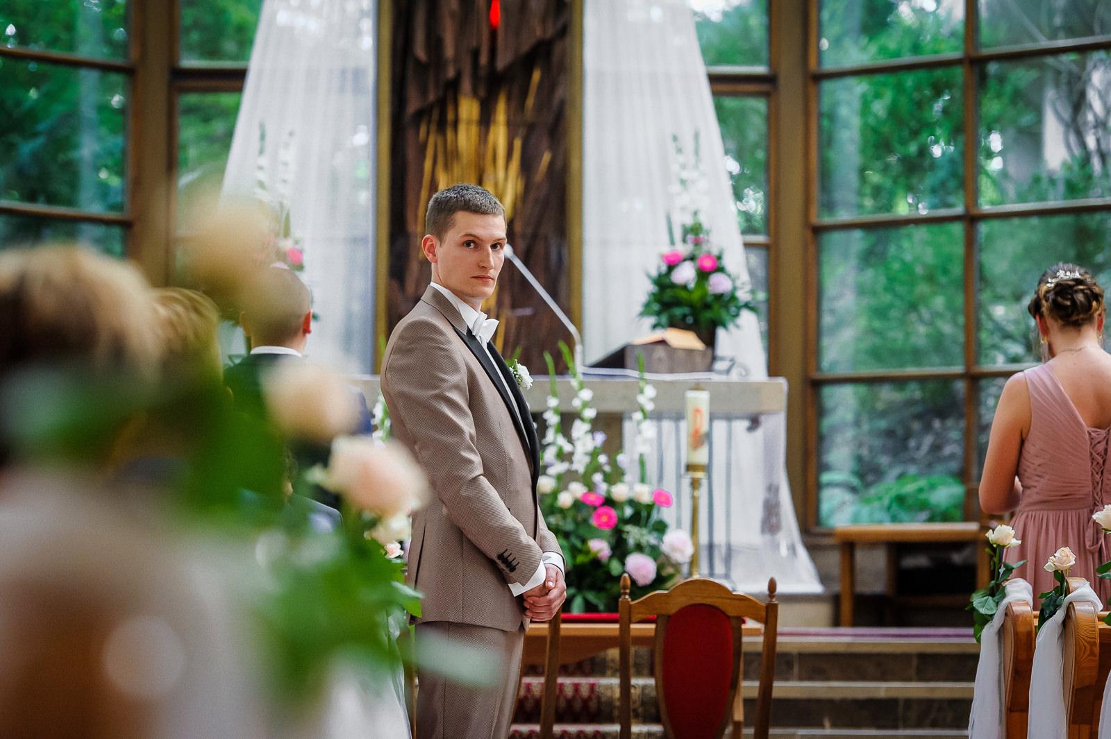 Na pamiątkowej fotografii ślubnej doskonale widać emocje Pana młodego oczekującego na swoja wybranką przy ołtarzu.