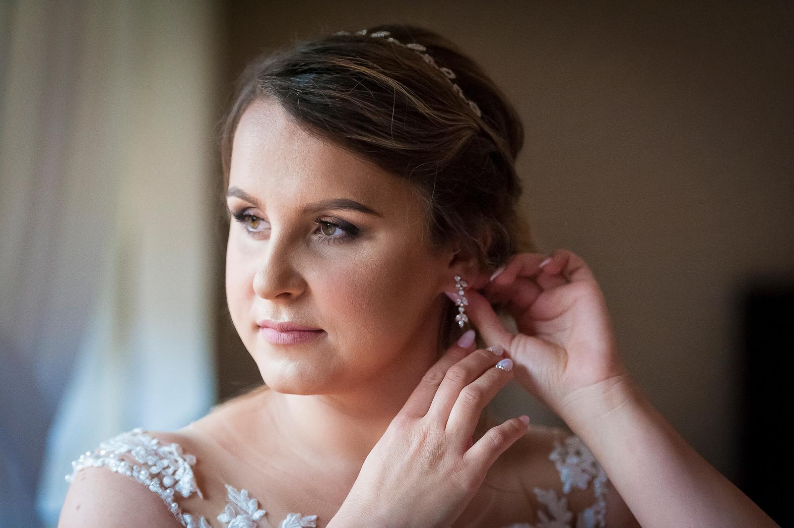 Ostatnie poprawki przed wyjściem do kościoła to dobry moment na uchwycenie kilku kadrów przez fotografa ślubnego.