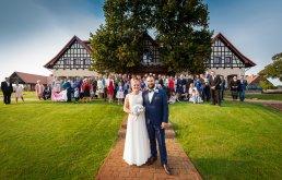 Wysunięcie pary młodej na pierwszy plan podczas pamiątkowego zdjecia grupowego pozwala fotografowi ślubnemu bardziej wyróżnić ich na zdjęciu do albumu ślubnego.