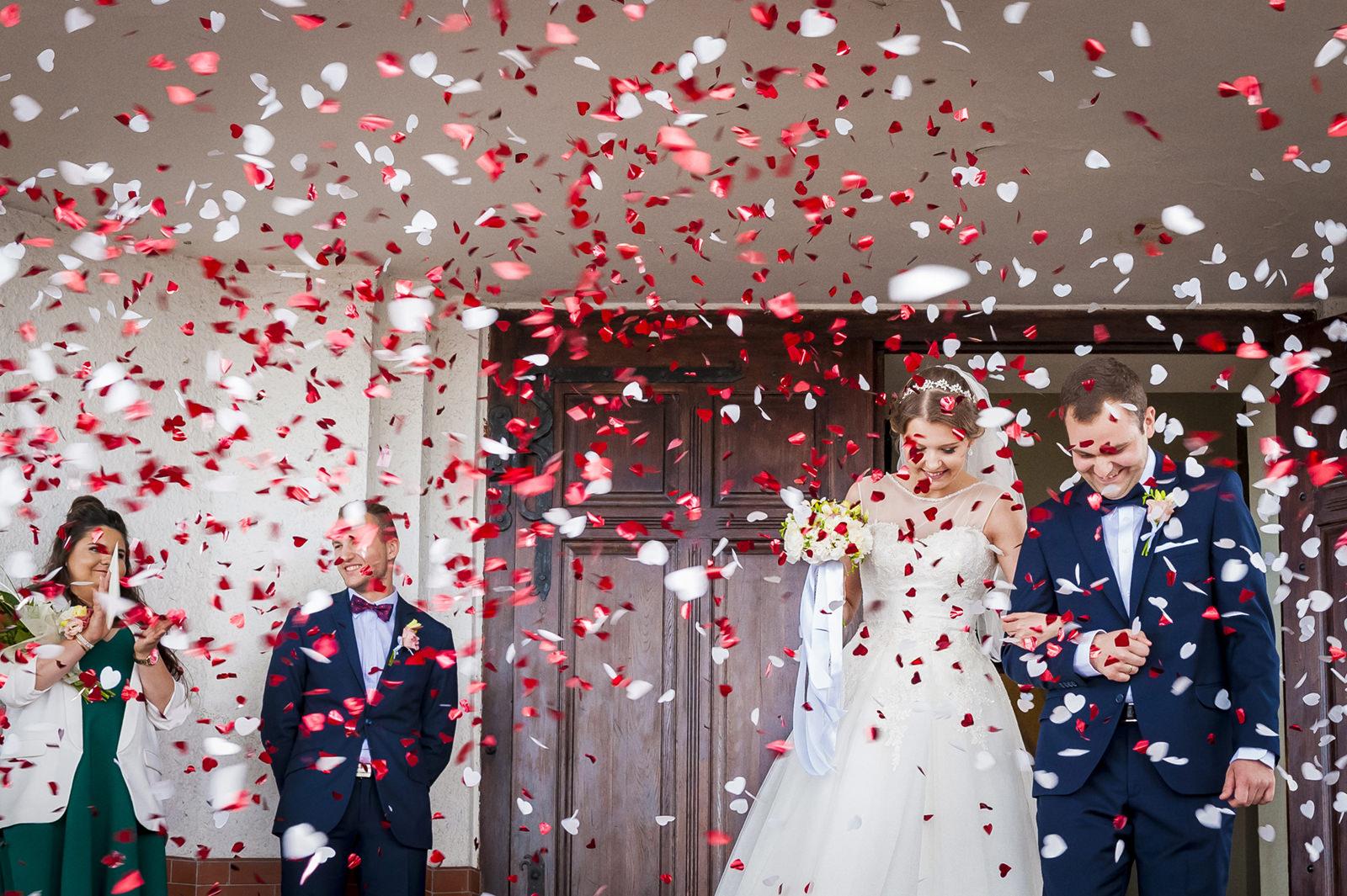 Wyjście parzy młodej z kościoła to dla fotografa ślubnego okazja na uchwycenie wybuchu radości i wystrzału konfetti.