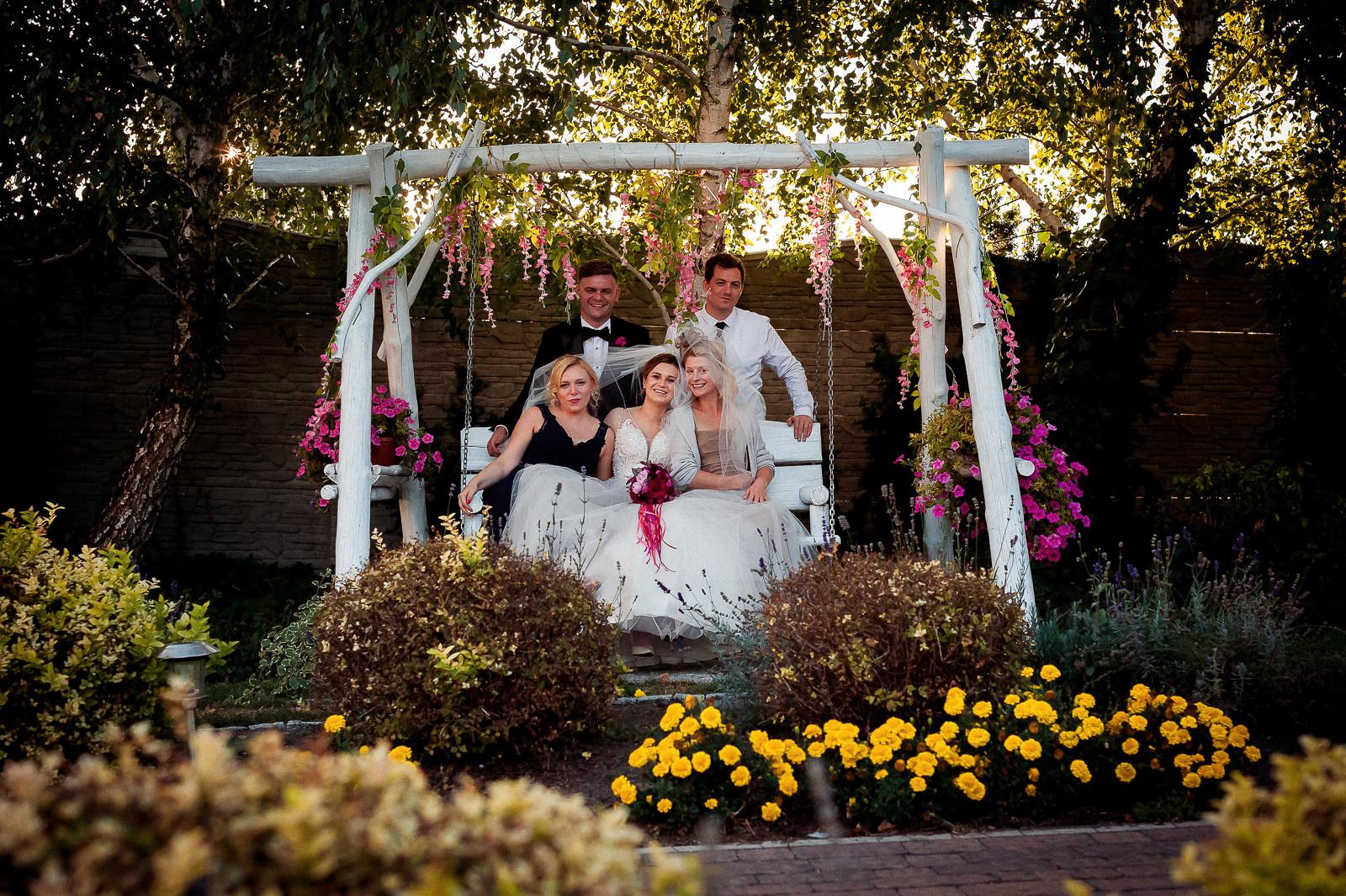 Pamiątkowe zdjęcia w grupach wychodzą najbardziej naturalnie, jeśli fotograf ślubny wykorzysta dostępne na miejscu walory otoczenia.