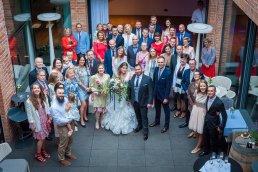 Zdjecia grupowe ze ślubu bardzo dobrze wychodzą, kiedy fotograf jest wyżej od zebranych osób, np. na tarasie w hotelowym patio.