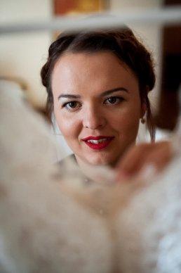 spojrzenie panny młodej na jej suknię ślubną ujęte na fotografii ślubnej