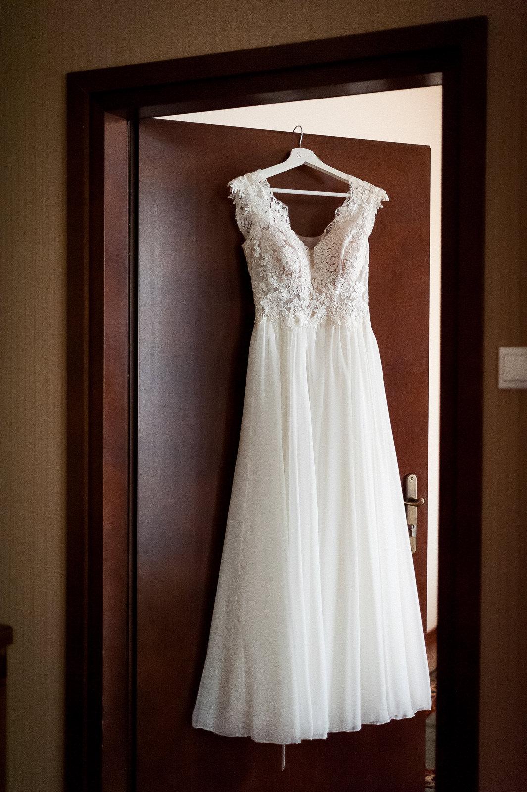 fotografia Sukni ślubnej zawieszonej na drzwiach pokoju wymownie świadczy o podniosłości chwili i o tym co niebawem wydarzy się w życiu dwojga zakochanych w sobie ludzi