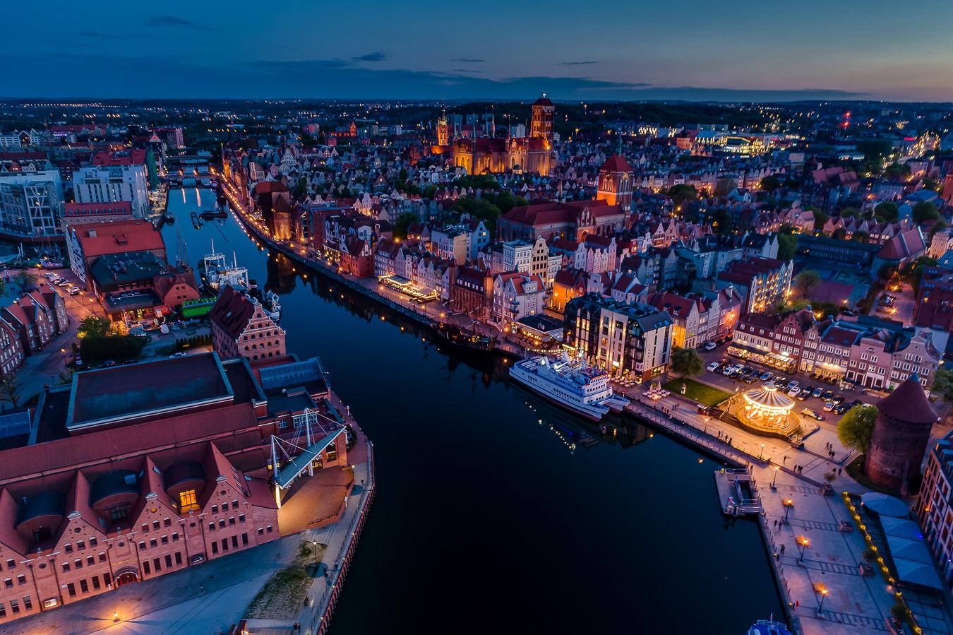 Gdańsk - widok z drona na Motławę rozdzielającą Filharmonię Bałtycką na Ołowiance oraz Rybackie Pobrzeże i karuzelę na Targu Rybnym