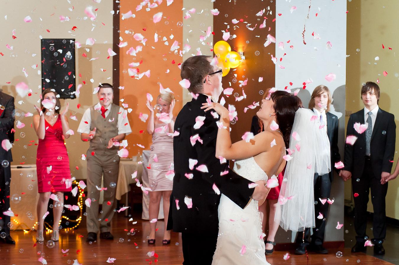 para młoda obsypana płatkami kwiatów podczas pierwszego tańca