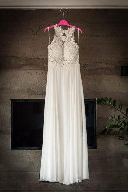 ślubna suknia w stylu boho czeka na wieszaku