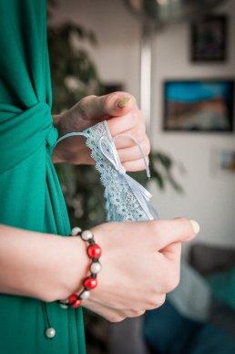 druhna pomaga założyć pannie młodej koronkową podwiązkę