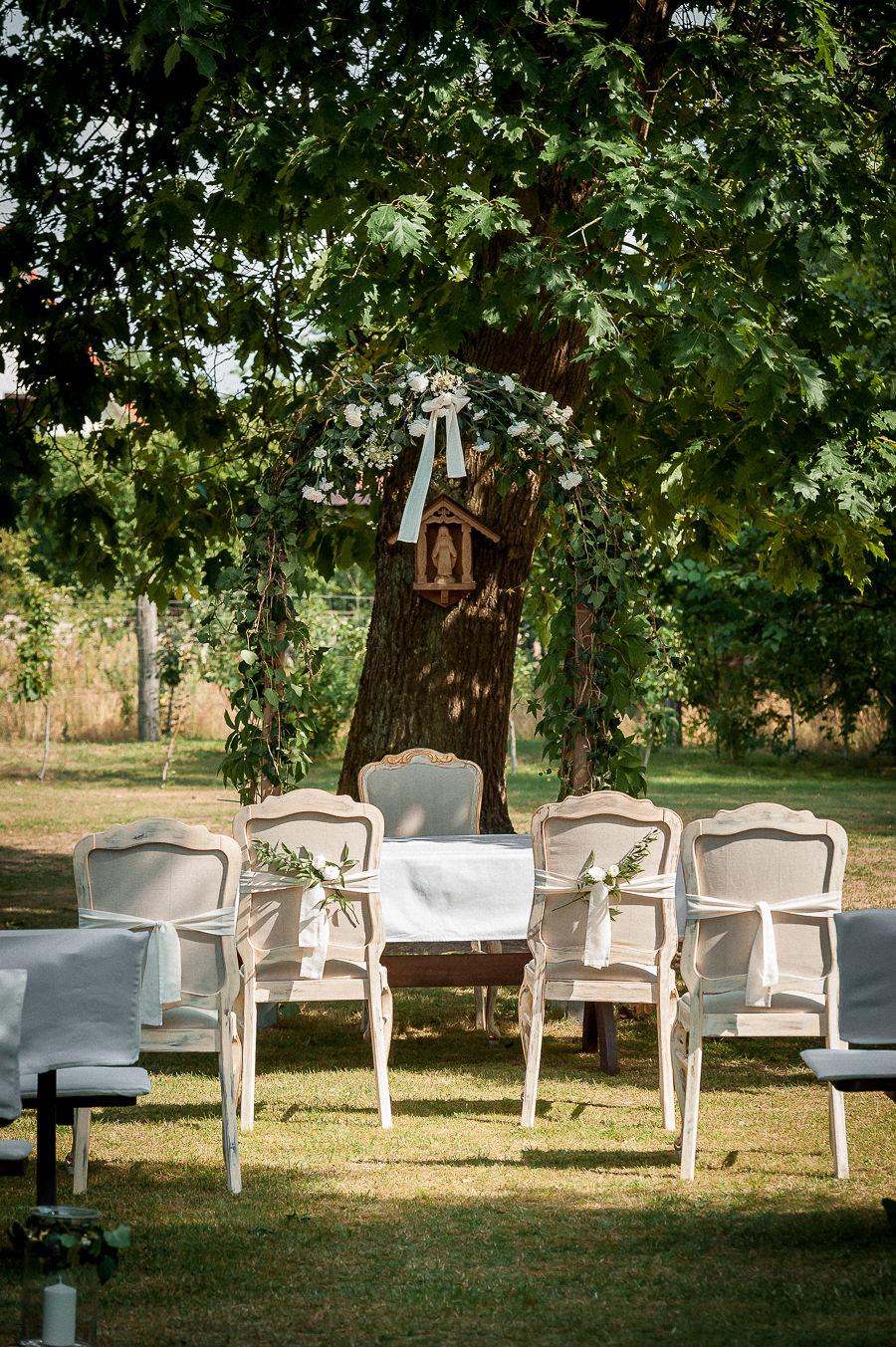 krzesła i stół prezydialny oczekujace na ślub w plenerze