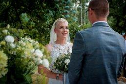 panna młoda w otoczeniu zieleni ogrodu na ślubie w plenerze