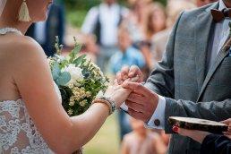 pan młody zakłada obrączkę podczas ślubu w plenerze
