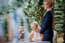 moment podpisania dokumentów po zawarciu związku małżeńskiego w otoczeniu przyrody